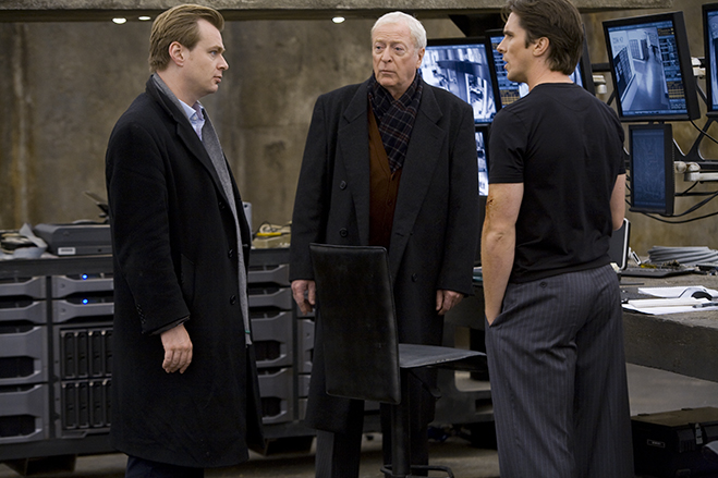 on the set of 2008's The Dark Knight, director Christopher Nolan discusses a scene with Michael Caine as Alfred and Christian Bale as Bruce Wayne.