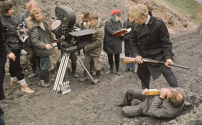 Ian Hendry as Eric Paice laying on the ground holding bottle and Michael Caine as Jack Carter holding gun/shotgun standing above him while crew members look on.
