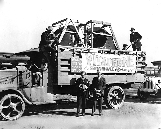 In this 1926 photo, Sid Grauman and Jack L. Warner stand in front of a truck containing the first Vitaphone sound equipment to be placed in Grauman's Egyptian Theater in Hollywood, under guard (with guns/rifles) by Bill Guthrie and Captain Carillo.