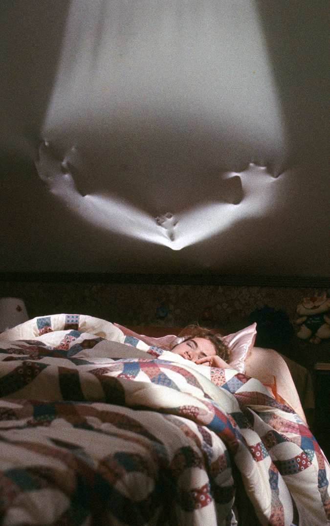 Heather Langenkamp as Nancy Thompson lies in bed unaware of the shape of Freddy Krueger coming through the wall.
