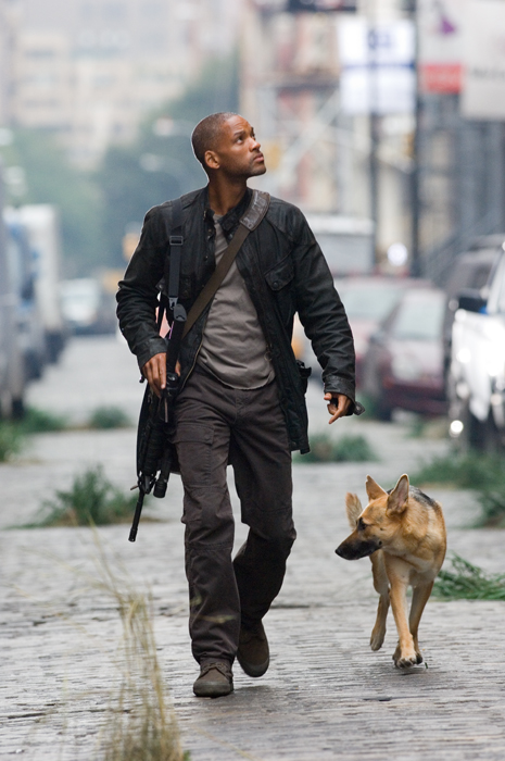 Will Smith as Robert Neville, carrying gun and walking with dog