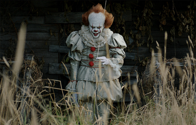 Pennywise the clown from It staring straight ahead and grinning, holding balloon