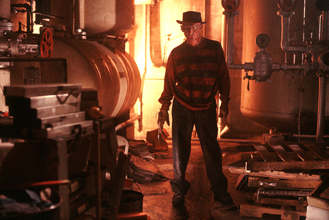 Robert Englund as Freddy Krueger standing in the boiler room.