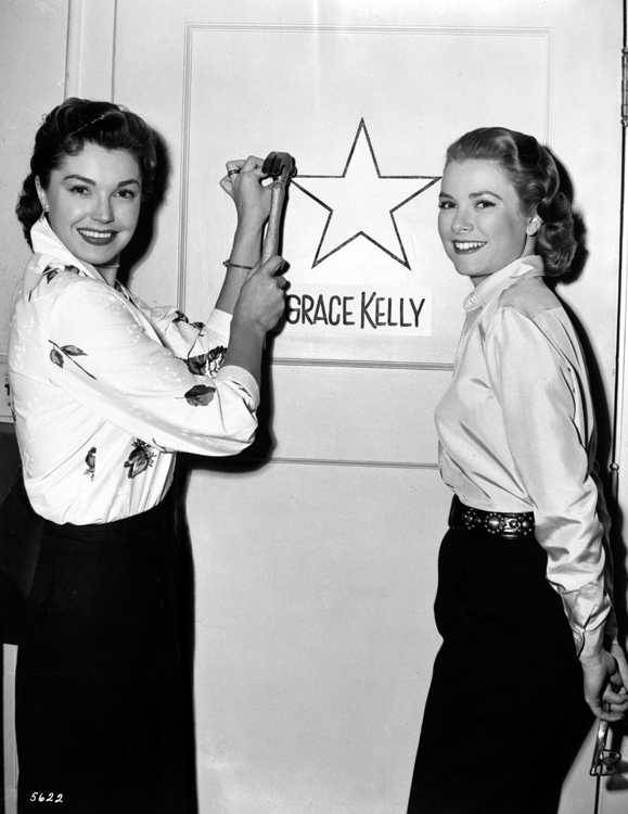 Grace Kelly hangs a star on her dressing room with Esther Williams