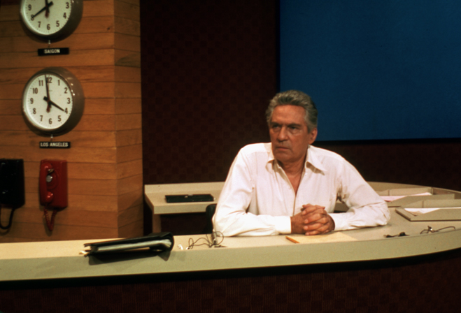 Medium shot of Peter Finch as Howard Beale sitting at News Desk.