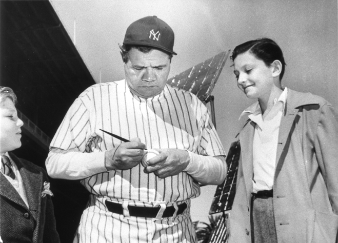Babe Ruth signing a baseball