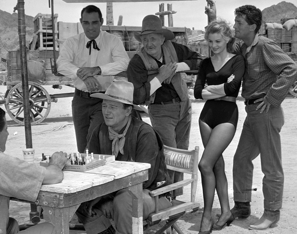 Rio Bravo John Wayne plays chess against a crew member while John Russell as Nathan Burdette, Walter Brennan, Angie Dickinson, and Dean Martin