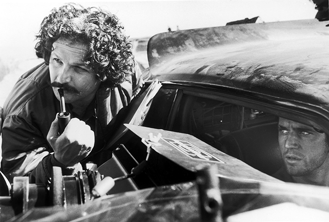 director george miller and mel gibson discuss a scene on the set of mad max: the road warrior