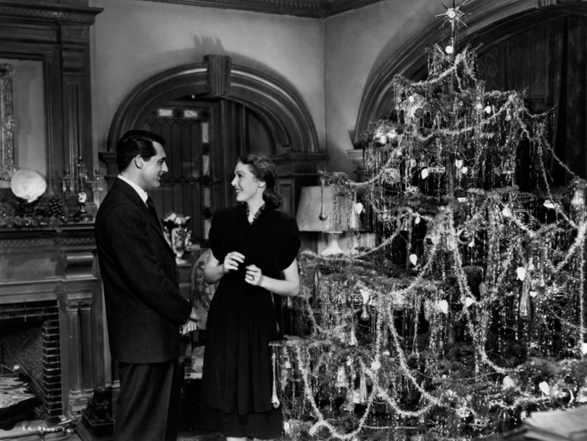 Cary Grant and Loretta Young standing next to a Christmas tree