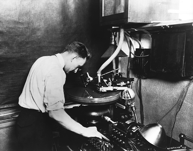 Sound Department worker George Groves, with Vitaphone sound-on-disc equipment, late 1920s.