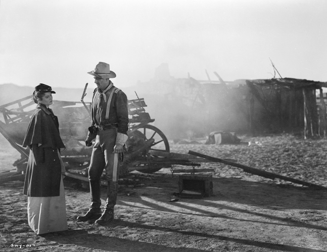 Olivia Dandridge as Joanne Dru and John Wayne as Captain Nathan Brittles, standing by broken-down wagon.