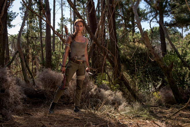ALICIA VIKANDER as Lara Croft standing in a forest