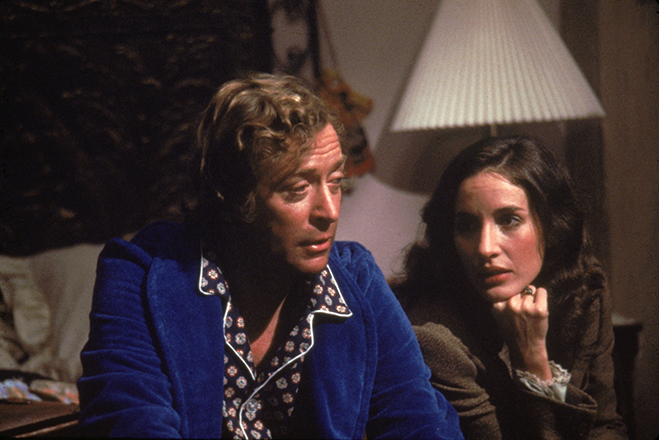 Wearing quite the wardrobe, Caine is pictured with Andrea Marcovicci on the set of Oliver Stone's horror flick, The Hand