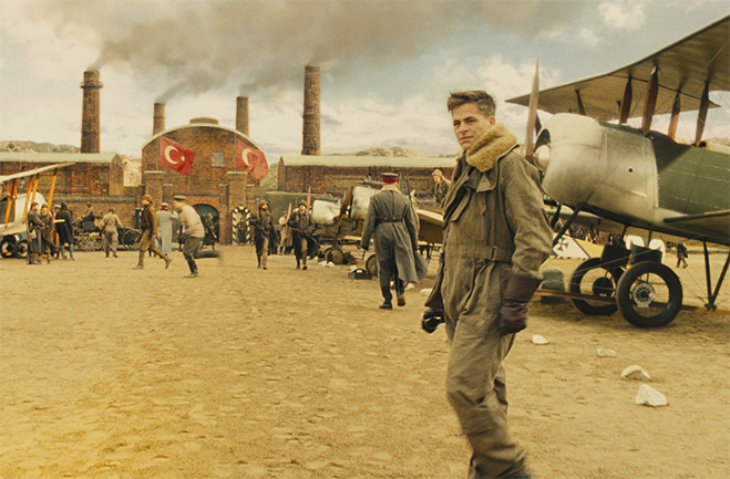 Steve Trevor in pilot uniform standing in front of WWI airplane