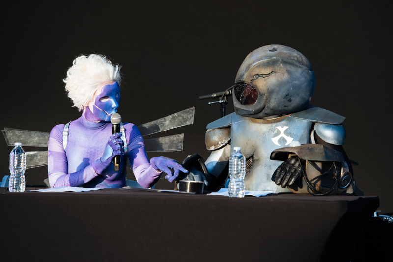 Adult Swim Festival - Toonami - Girl in blond curly wig with purple one pice suit talking on mic with an alien in spacesuit