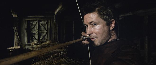 Aidan Gillen as Goosefat Bill aiming a bow and arrow in King Arthur: Legend of the Sword
