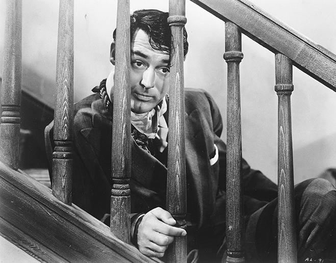 Cary Grant as Mortimer Brewster looking through staircase.