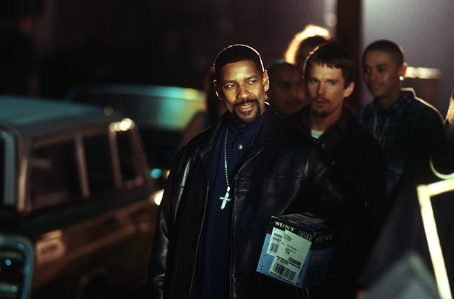 Medium shot of smiling Denzel Washington as Alonzo Harris standing in front of Ethan Hawke as Jake Hoyt, with man standing behind.