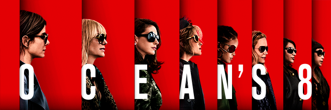 Cast of Ocean's 8 in profile wearing dark glass and coats on red background