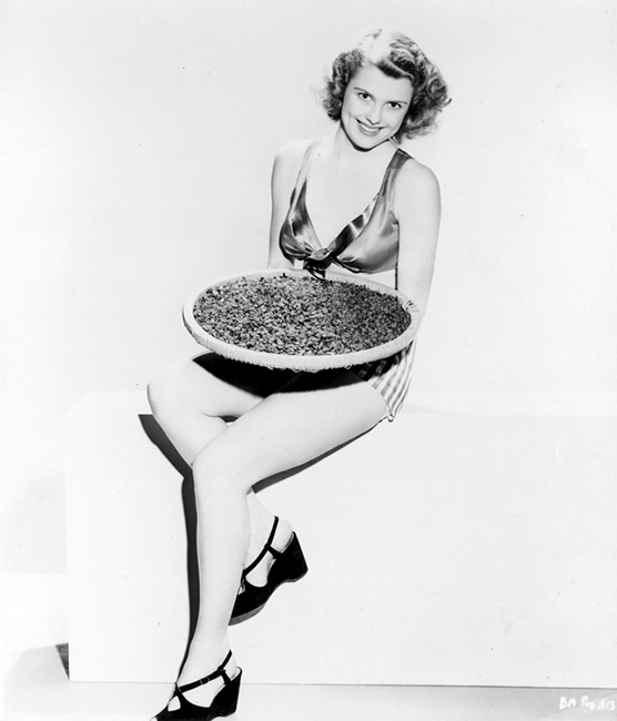 Full publicity shot of Betty Alexander, holding pizza.