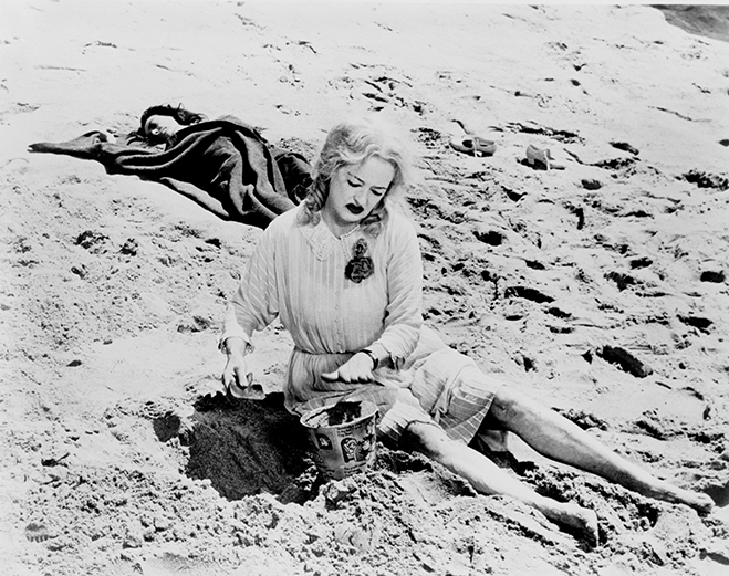 Full shot of Bette Davis as Jane Hudson putting sand into bucket with small shovel as Joan Crawford as Blanche Hudson lies in sand in background.