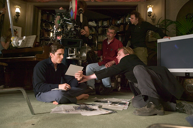 Christian Bale and director Christopher Nolan go over notes during a scene for 2005's Batman Begins.