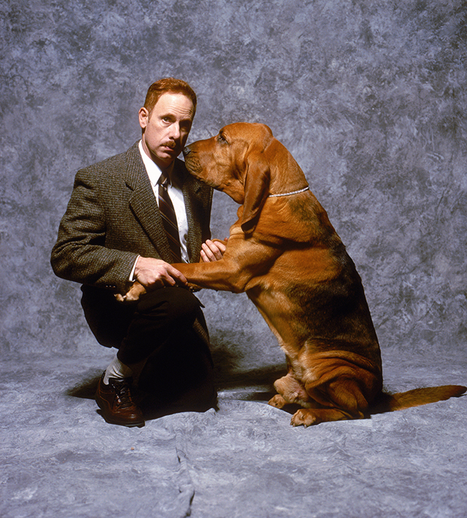 Full publicity shot of kneeling Christopher Guest as Harlan Pepper and dog/Bloodhound.