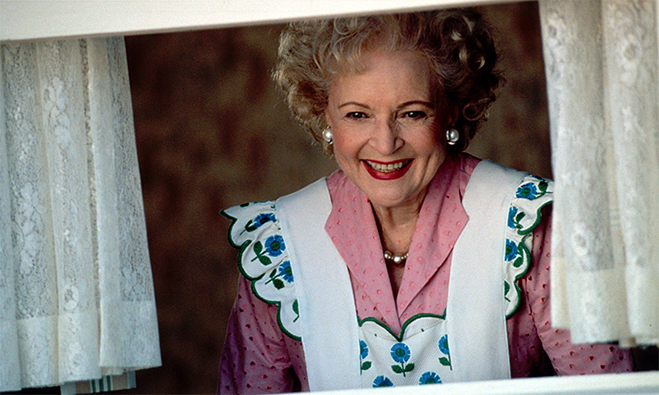 Betty White wearing an apron and looking out the window as Mrs. Wilson in Dennis the Menace