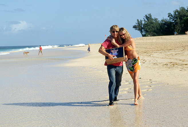 owen wilson and sara foster, with refreshments in hand, stroll on the beach in comedy crime caper, The Big Bounce.