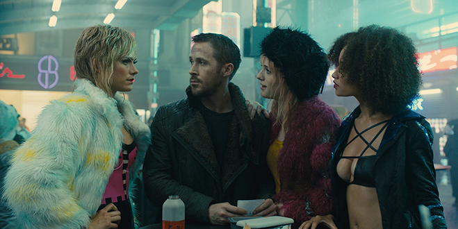 RYAN GOSLING as K and MACKENZIE DAVIS as Mariette in a street scene.