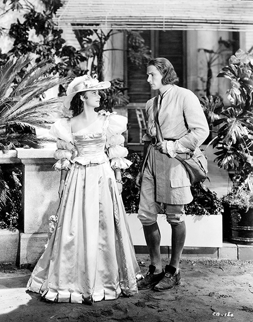 Sumptuously costumed de Havilland as Arabella Bishop and Flynn as Dr. Peter Blood in Captain Blood