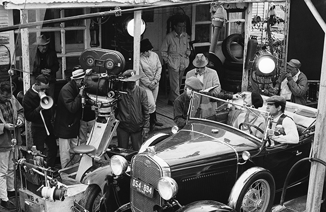 Michael J. Pollard, Faye Dunaway and Warren Beatty with the set crew shooting the gas station scene (seen in the video clip above).
