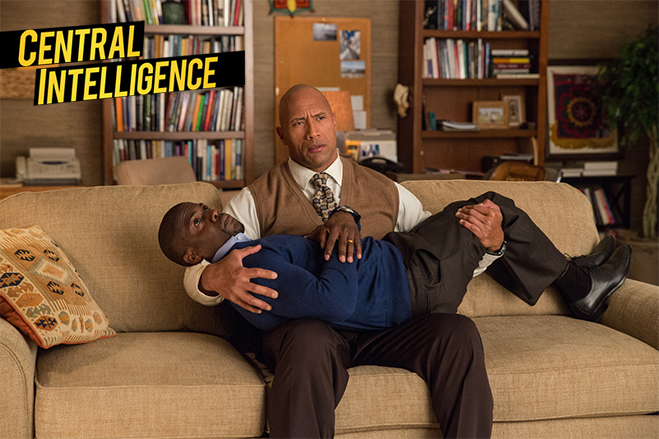 Kevin Hart being cradled by Dwayne Johnson on a couch in Central Intelligence