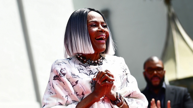 Cicely Tyson wearing a white dress with patterns, clapping her hands, laughing