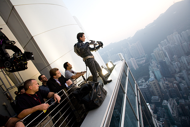 Sans the trademark cowl, Christian Bale prepares for a shot on the set of 2008's blockbuster The Dark Knight as director Christopher Nolan and crew look on.