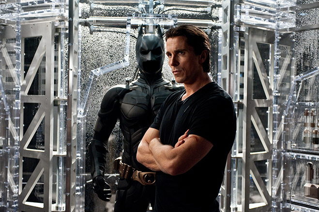 Christian Bale as Bruce Wayne stands in front of his alter ego costume for the last time in 2012's The Dark Knight Rises.