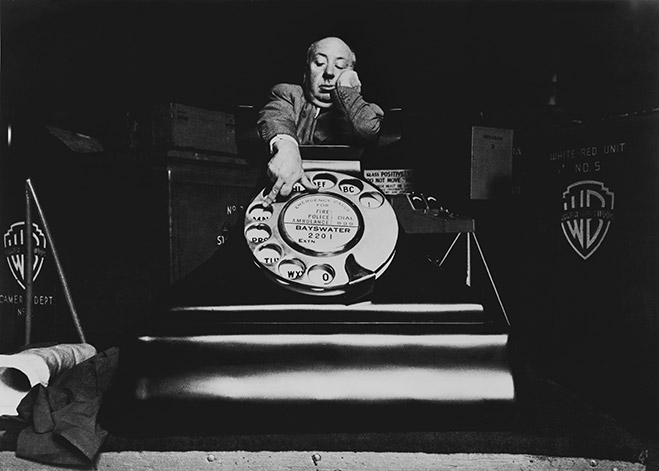 Alfred Hitchcock standing behind oversize prop telephone.