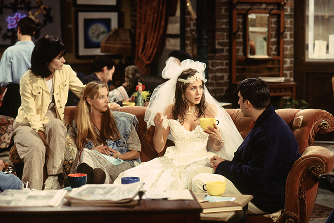 Monica, Phoebe, Rachel (wearing wedding dress) and Ross, all sitting on couch in Central Perk coffee house