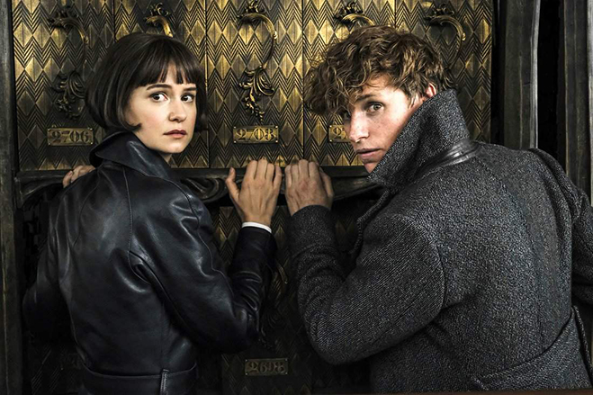 Tina Goldstein and Newt Scamander look behind them