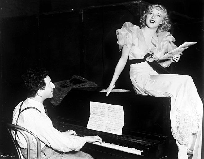 Mark Sandrich, seated, playing piano, with Ginger Rogers as Mimi sitting atop piano in The Gay Divorcee