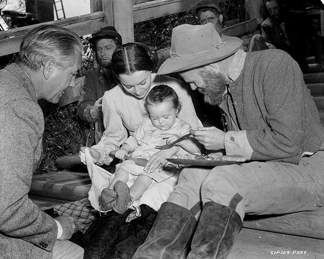 Behind-the-scenes with de Havilland and Ric Holt as Beau Wilkes (11 months) seated on her lap. Alongside her are director Victor Fleming and Phillip Trent as a hungry solider.