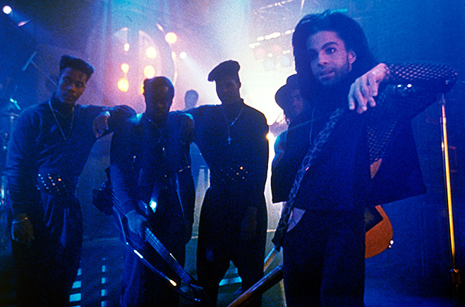 Prince as The Kid leaning on microphone stand, and standing with band members.