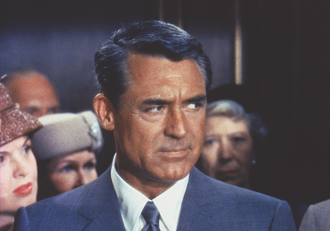 cary grant with a distrustful look towards those around him in north by northwest