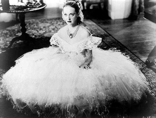 Full shot of Bette Davis as Julie Marsden sitting on floor, wearing long white dress.