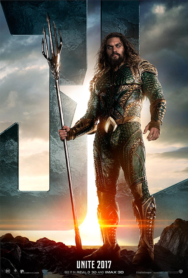 Jason Momoa as Aquaman standing in front of JL letters on a beach shoreline holding spear