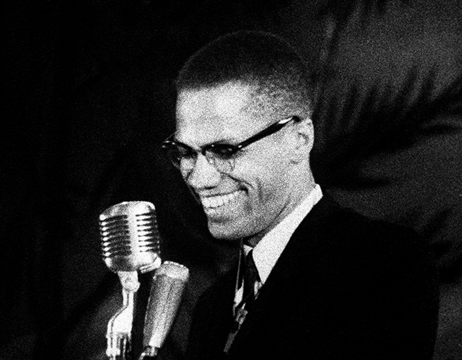 Malcolm X smiling and standing behind a microphone