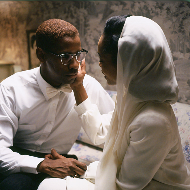 Medium shot of Angela Bassett as Betty Shabazz wearing a white robe and head covering, touching the face of Denzel Washington as Malcolm X.