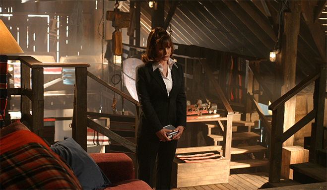 Full shot of Margot Kidder as Bridgette Crosby, standing in barn, holding box.