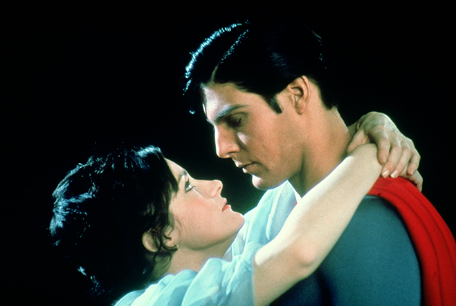Medium profile shot of Margot Kidder as Lois Lane with arms around neck of Christopher Reeve as Superman.