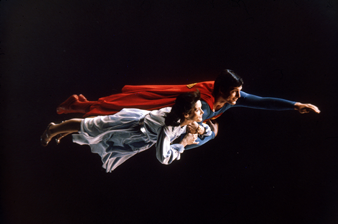 Full profile shot of Christopher Reeve as Superman flying with Margot Kidder as Lois Lane.